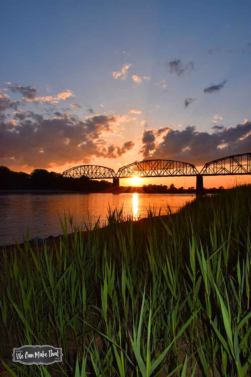Railroad bridge over river at sunset